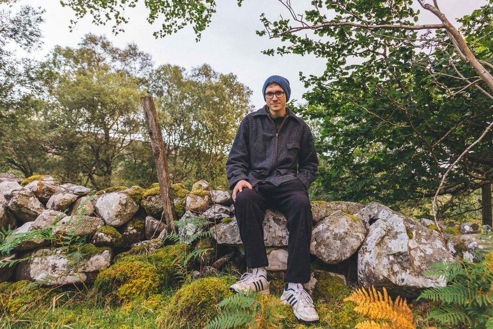 adrian shelley sitting on rock wall